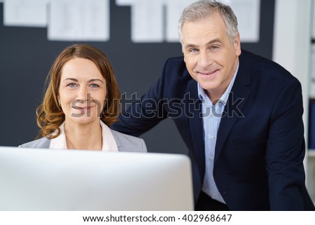 Smiling happy business partners or co-workers, with a middle-aged man and woman, seated behind a desktop computer looking at the camera - stock photo
