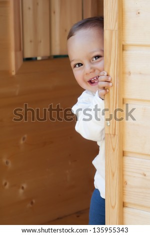 Smiling happy child playing with a door in a wooden playhouse or a small garden shed. - stock photo