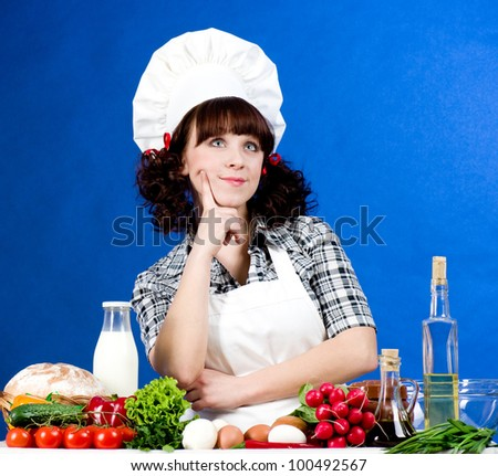 Smiling happy cook woman with food ingredients - stock photo
