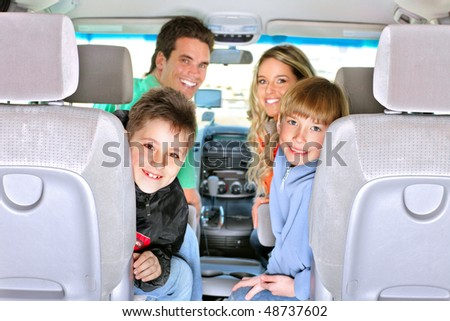 Smiling happy family in the car - stock photo