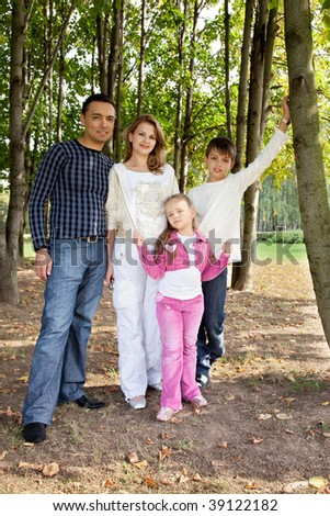 smiling happy family of four in park - stock photo