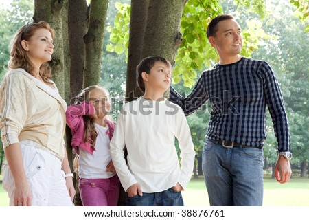smiling happy family of four looking aside outdoors - stock photo