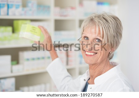 Smiling happy female pharmacist reaching for medication on the shelf and displaying it to the camera - stock photo