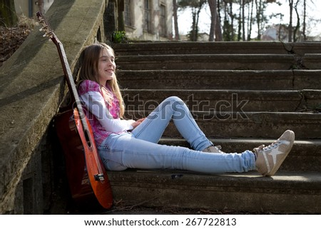 Smiling Happy Girl Casually Dressed Sitting on the Stairs in Park and Resting on Sunny Spring Day.  - stock photo
