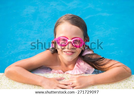 Smiling happy girl in goggles for swimming at outdoor pool - stock photo