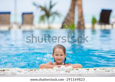 Smiling happy girl in outdoor swimming pool - stock photo