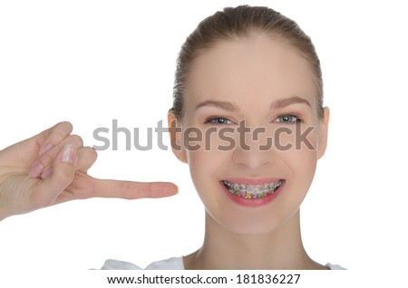 Smiling happy girl indicates braces on teeth isolated on white - stock photo