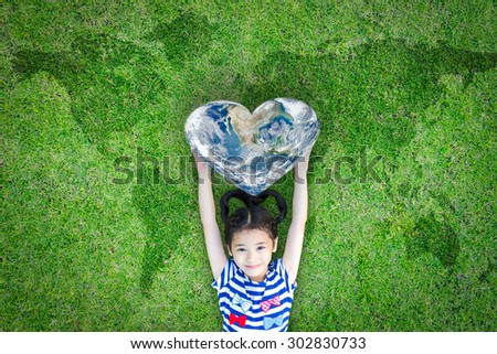 Smiling happy healthy child kid holding heart shaped globe on eco world map grass background: World heart day concept and promoting global health csr campaign: Elements of this image furnished by NASA - stock photo