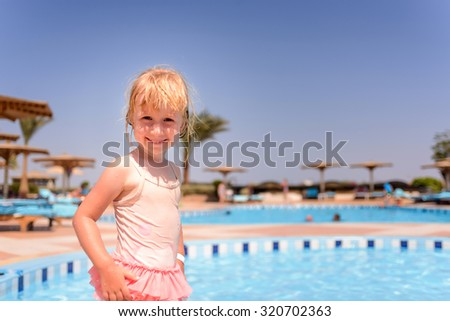 Smiling happy little blond girl at a resort swimming pool standing in her pink swimsuit grinning at the camera on summer vacation, with copyspace - stock photo