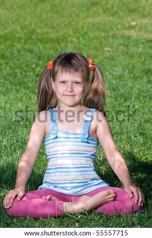 Smiling happy little cute girl who is sitting and meditating in yoga lotus asana under tree shadow on the green grass - stock photo
