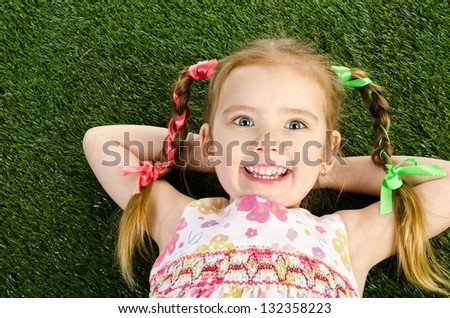 Smiling happy little girl lying on grass - stock photo