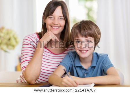 Smiling happy mother and young son sitting close together at the dining table working on paperwork or homework from school - stock photo