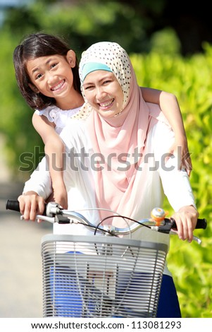 smiling happy mother with her daughter riding bicycle - stock photo