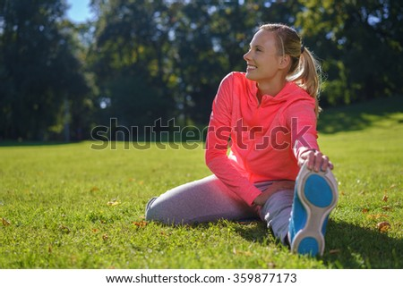 Smiling happy pretty young woman doing stretching exercises outdoors as she sits on the green grass in the park enjoying a day in nature - stock photo