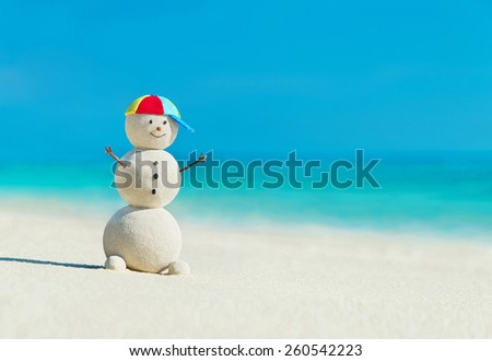 Smiling happy sandy snowman in rainbow peaked hat on sea beach against blue summer sky - travel vacation concept - stock photo