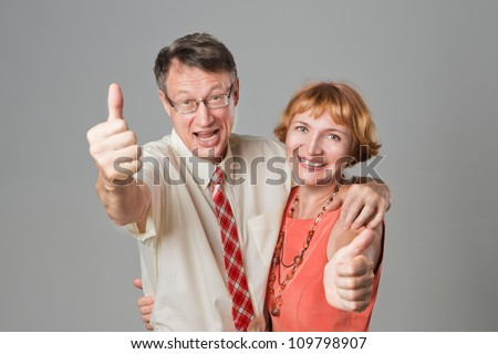 Smiling happy senior couple with thumbs up. Healthy teeth. - stock photo
