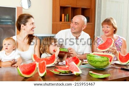 Smiling happy three generations family eating watermelon  - stock photo