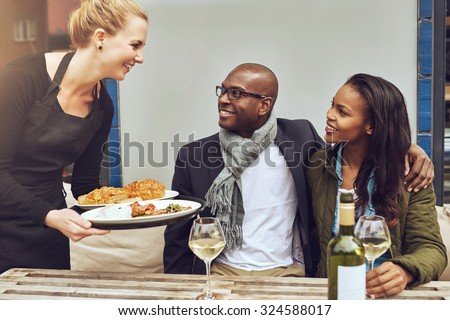 Smiling happy young Caucasian waitress serving a loving African American couple dinner as they sit arm in arm at a table in a restaurant - stock photo