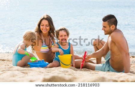 Smiling happy young family of four resting at seashore in sunny day - stock photo