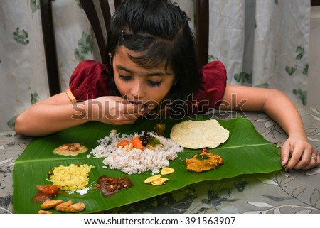 Smiling/ happy young Indian girl / child / kids wearing traditional dress eating Onam sadhya with hand for festival, Kerala India. Asian child. Beautiful daughter in traditional Indian sari on Vishu   - stock photo