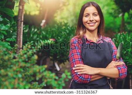 Smiling happy young woman enjoying her garden standing with folded arms against lush greenery with a trowel in her hand looking at the camera with a beaming smile - stock photo