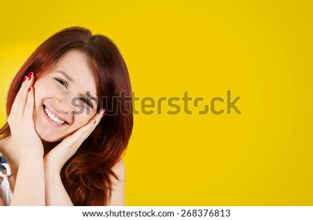 Smiling Happy  young woman holding her hands on her face in and looking at the camera isolated on yellow background. - stock photo