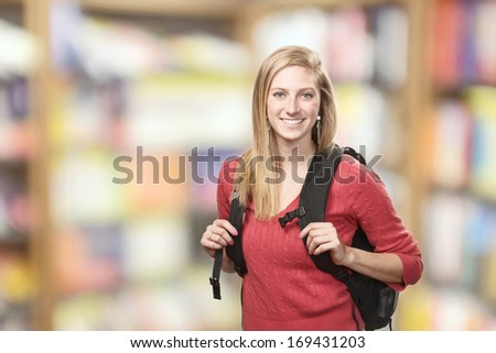 Smiling happy young woman student in library - stock photo