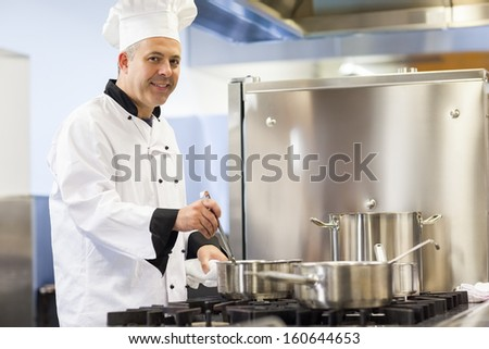 Smiling head chef stirring in pot in professional kitchen - stock photo