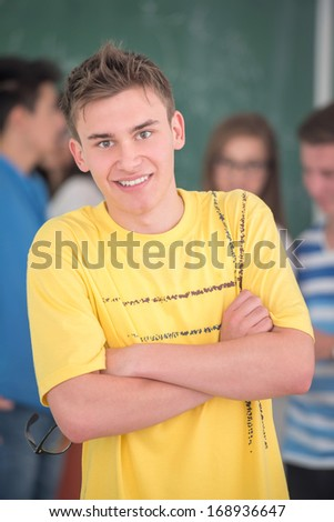 Smiling highschool student posing in classroom - stock photo