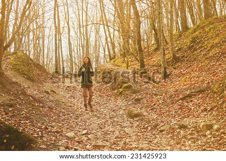 Smiling hiker woman walking in beautiful autumn forest, dry yellow leaves on land. Hiking and leisure theme. Image with sunlight effect - stock photo