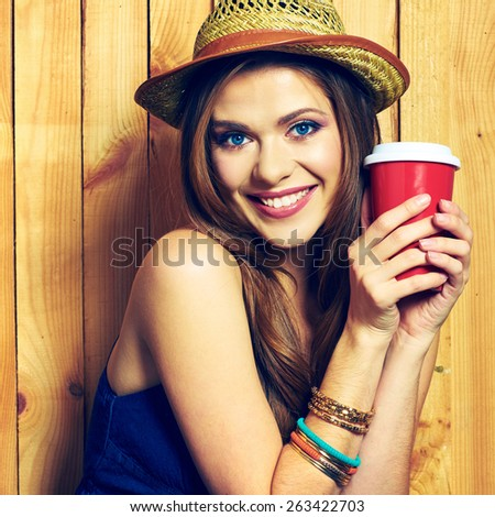 Smiling Hipster Girl Holding Coffee Cup. Yellow hat. Teeth smiling model with long hair. - stock photo