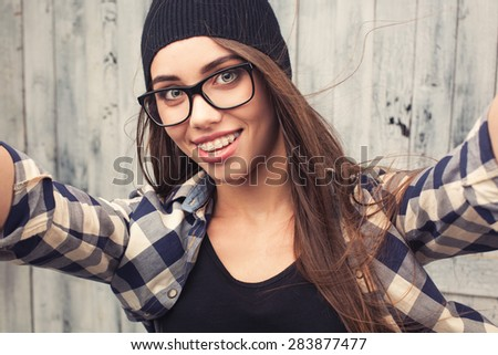 smiling Hipster girl in glasses and braces making a selfshoot on wooden background - stock photo