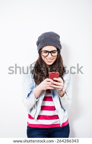 Smiling hipster girl Texting on Cell Phone. Sending SMS, text message  - stock photo