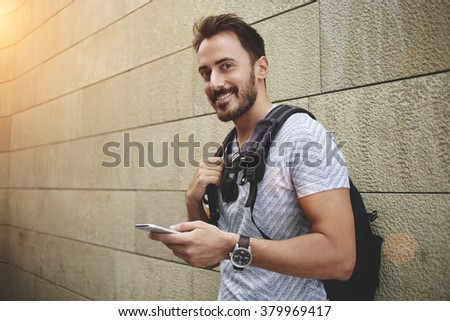 Smiling hipster guy holding mobile phone and looking at the camera while waiting for someone outdoors,cheerful man wanderer use cell telephone while standing against street wall with copy space area - stock photo