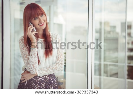 Smiling hipster woman having a phone call in office - stock photo