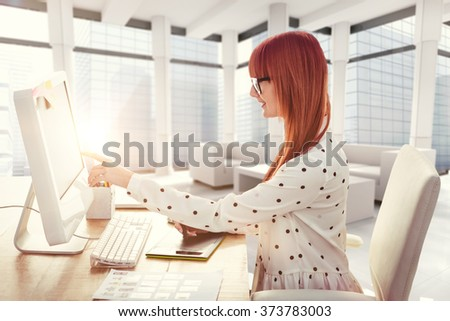 Smiling hipster woman using graphics tablet and pointing screen against modern room overlooking city - stock photo