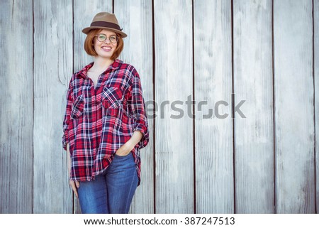 smiling hipster woman with her hand in her pocket, against a wooden background - stock photo