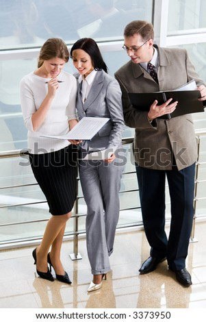 Smiling Hispanic businesswoman giving advices to her colleague and curious businessman in eyeglasses with opened paper case in his hands - stock photo