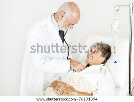 Smiling hospital patient gets examined by handsome doctor. - stock photo