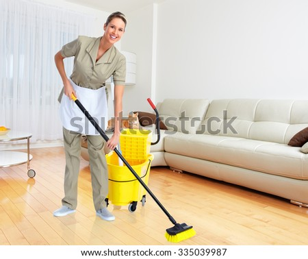Smiling housewife cleaner with broom in modern apartment background - stock photo