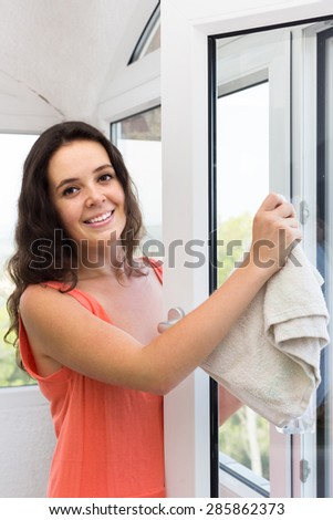 Smiling housewife cleaning windows using atomizer indoor