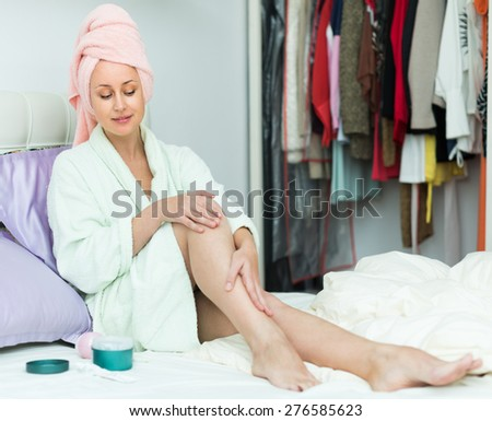 Smiling housewife sitting on bed and applying cream on her legs skin - stock photo