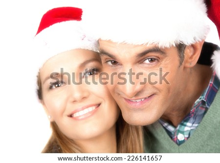 Smiling husband and wife with Christmas red hats, isolated on white. Christmas and happiness concept. - stock photo