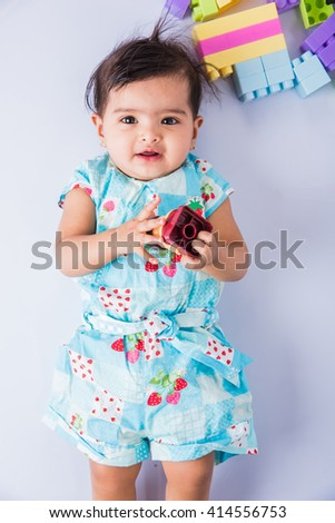 smiling indian baby girl on the floor, top view, asian infant or new born girl, smiling, Adorable little baby girl laying on white background. Little baby girl smiling and looking at the camera - stock photo