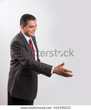 Smiling Indian businessman outstretching hand for a handshake, asian businessman offering hand shake or shake hand or shakehand - stock photo