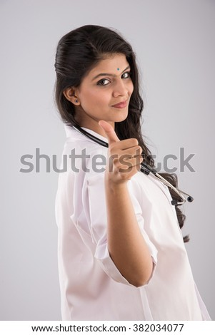 smiling indian doctor with stethoscope, woman health care professional giving OK sign, isolated, Positive face expression, emotion attitude, indian or asian confident female doctor - stock photo