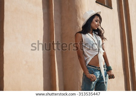 smiling indian lady in jeans, white shirt and white hat against ancient building. She is in harsh morning light. She is positive and playful.  - stock photo