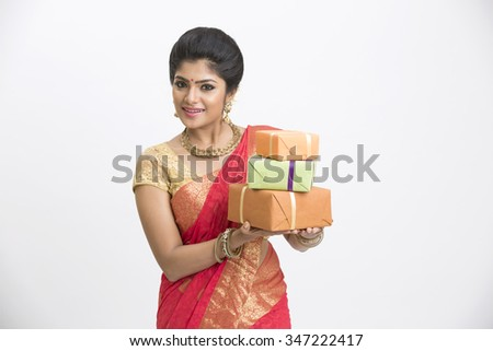 Smiling Indian woman in traditional south indian saree holding gifts  - stock photo