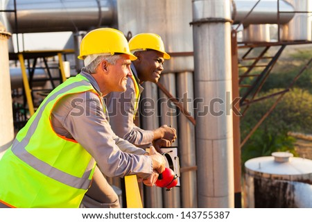 smiling industrial workers in safety gear - stock photo