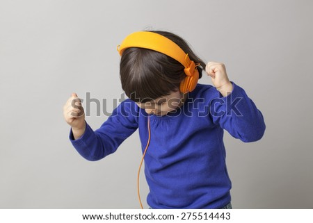 smiling infant with headphones focusing on rhythm and music - stock photo